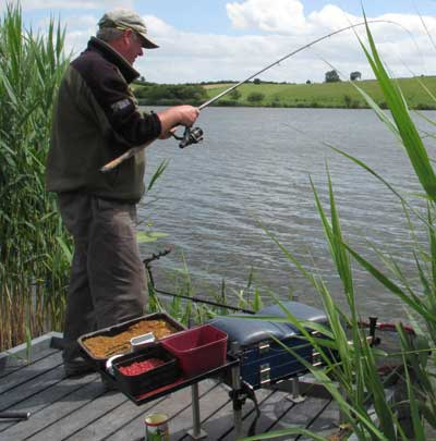 Peadar O' Brien playing a large bream, County Monaghan, Ireland.