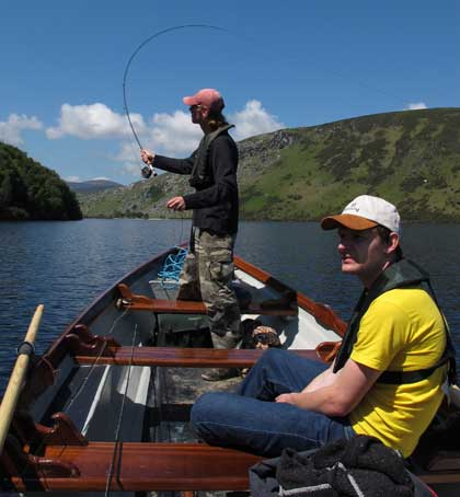Casting a line towards a shaded bank, Lough Dan, Co. Wicklow, Ireland.