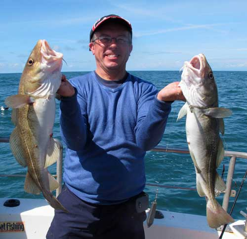 A happy Welsh angler with a brace of codling boated off Kilmore Quay, Co. Wexford, Ireland.
