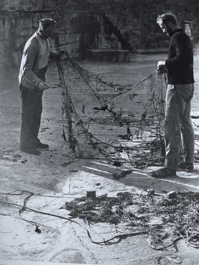 "Willie Redmond (left) and Seamus ""Jago"" Hayden (right) clean a trammel net of weed, Greystones, Co. Wicklow, Ireland around 1960."