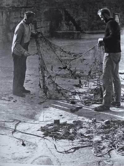 """Willie Redmond (left) and Seamus """"Jago"""" Hayden (right) clean a trammel net of weed, Greystones, Co. Wicklow, Ireland around 1960."""